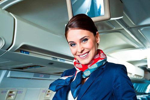 Flight Attendant smiling in a plane aisle.